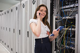 Smiling woman on the phone holding tablet pc and checking servers