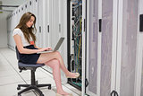 Woman working on servers with laptop