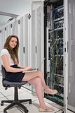 Happy woman with laptop working with servers