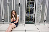 Woman sitting on the floor beside servers on the phone