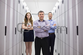 Three smiling technicians standing in data center