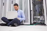 Man sitting on floor with laptop beside servers