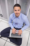 Smiling man using laptop in front of servers