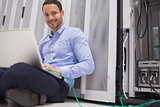 Happy technician working on laptop connected to server