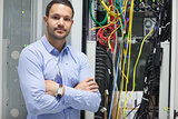 Man standing with arms crossed in data center
