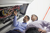 Technicians checking wires of server