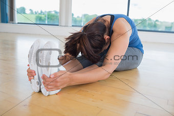 Woman in seated forward bend yoga pose
