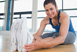 Smiling woman stretching legs