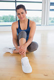 Happy woman sitting in fitness studio
