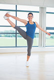 Woman doing extended hand to toe yoga pose
