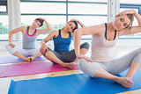 Women sitting and stretching at yoga class