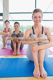 Happy women sitting on yoga mats