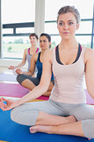 Women sitting on yoga mats at yoga class