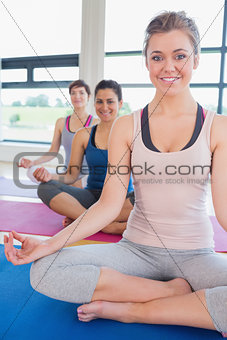 Happy women sitting in easy yoga pose