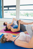Women in fitness studio stretching legs