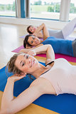 Women on mats doing sit ups