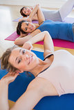 Smiling women doing sit ups