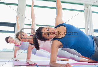 Women in side plank yoga pose