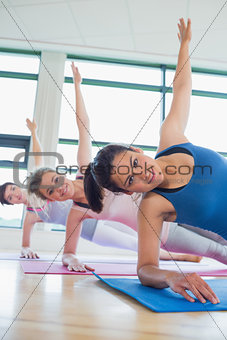 Happy women in side plank yoga pose