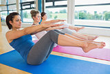 Women doing boat pose in yoga class