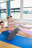 Women in yoga class doing boat pose