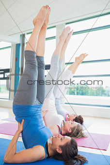 Women stretching backs at yoga class