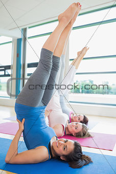 Smiling women stretching backs at yoga class
