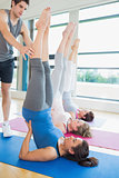 Trainer helping woman at yoga class