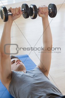 Man lifting dumbbells while lying