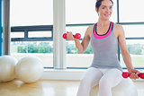 Happy woman lifting weights on exercise ball