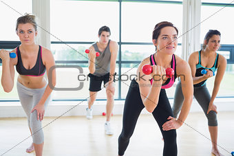 People lifting weights in aerobics class