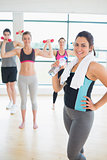 Smiling woman at front of aerobics class