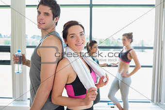 Man and woman standing back to back at the gym