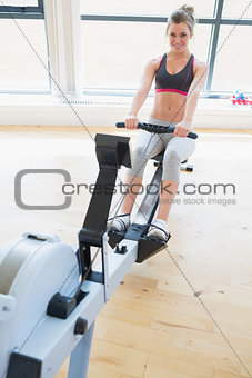 Woman sitting at the row machine pulling and smiling