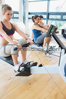 Man and women using the row machines
