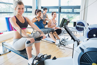 Smiling woman on rowing machine wi