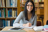 Smiling woman taking notes while doing research