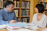 Man and woman talking in library