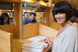 Black-haired woman reading a book in library