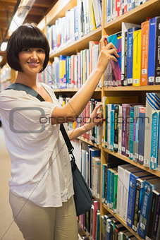 Black-haired woman taking a book out of the shelves