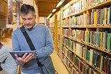 Man holding a tablet pc in a library