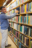 Man choosing book from shelf