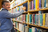 Smiling man taking a book from shelves