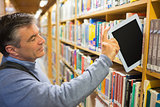 Man taking a tablet pc from the shelves