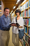 Happy man and woman standing in library