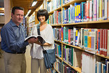 Man showing woman book in library
