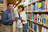 Man and woman standing in the library holding a tablet pc
