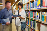Woman and man holding tablet pc in library