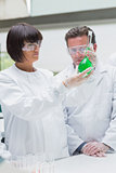 Chemists viewing green liquid
