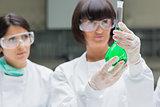 Female chemists viewing green liquid